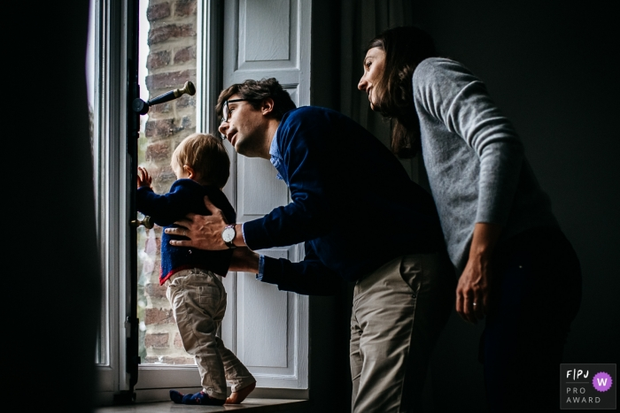 A mother and father help their son look out the window in this family picture by a Brabant Wallon photographer.