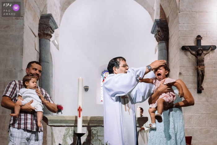 A priest attempts to bless an unhappy little girl as her mother holds her in this photograph created by a Paris, France family photojournalist.