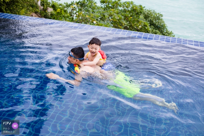 A little boy holds onto his father as they swim in a pool in this documentary-style family image recorded by a Hangzhou City photographer.