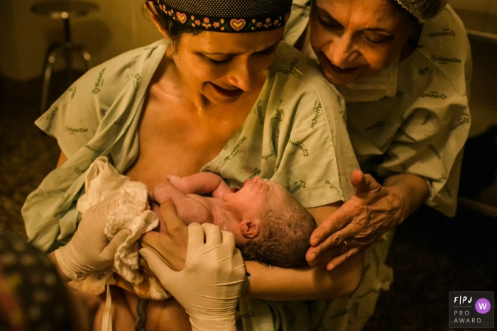 A mother holds her newborn in the hospital as her own mother comes to see in this image composed by an award-winning Minas Gerais birth photographer.