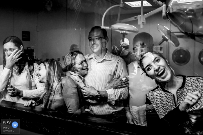A family looks through the hospital window to see their newborn family member in this black and white photo by a Minas Gerais, Brazil birth photographer.