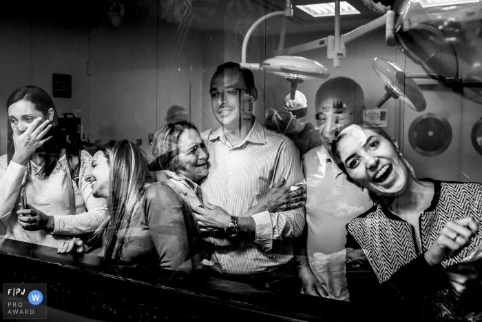 Une famille regarde par la fenêtre de l'hôpital un membre de la famille qui vient de naître sur cette photo en noir et blanc d'un photographe de naissance de Minas Gerais, au Brésil.