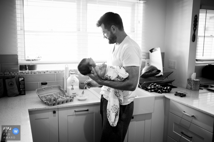 A father holds his infant while he makes breakfast in this award-winning photo by a Phoenix, AZ family photographer.