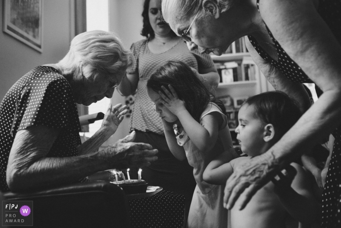 A little girl helps her grandmother blow out the candles on her birthday cake in this photograph created by a Rio de Janeiro, Brazil family photojournalist.