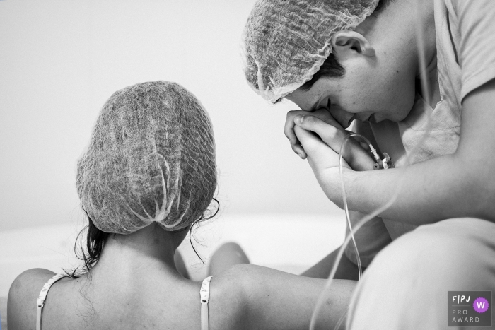 A husband holds his wife's hand in the hospital as she prepares to give birth in this black and white photo composed by an award-winning Minas Gerais, Brazil birth photographer.