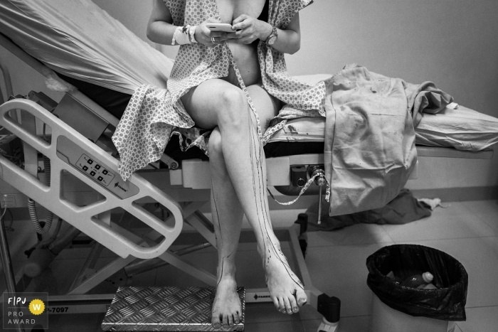 A pregnant woman sits on the edge of a hospital bed as she checks her phone in this black and white birth photo captured by a Minas Gerais, Brazil documentary photographer.