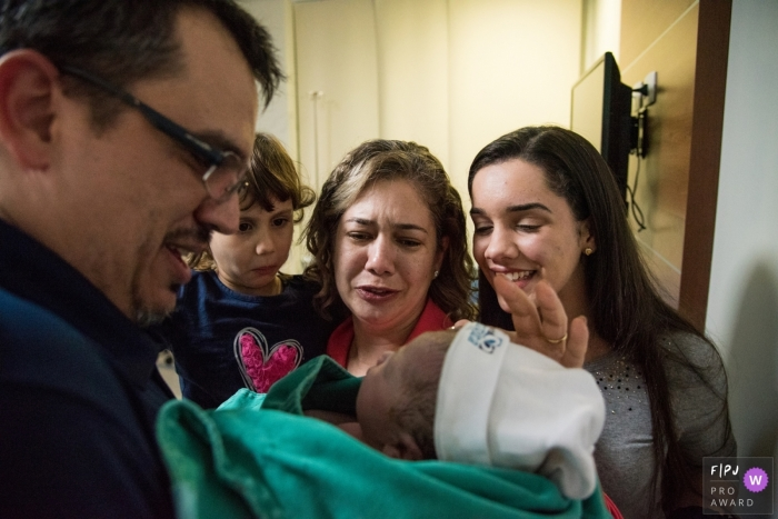 A family gets to meet their newest family member in the hospital in this photo by an award-winning Espirito Santo, Brazil birth photographer.