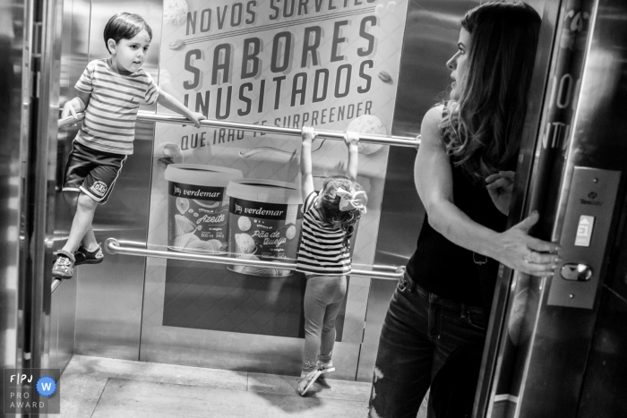 A mother holds elevator doors open as her children climb on the metal bars in this photograph by a Minas Gerais documentary family photographer.