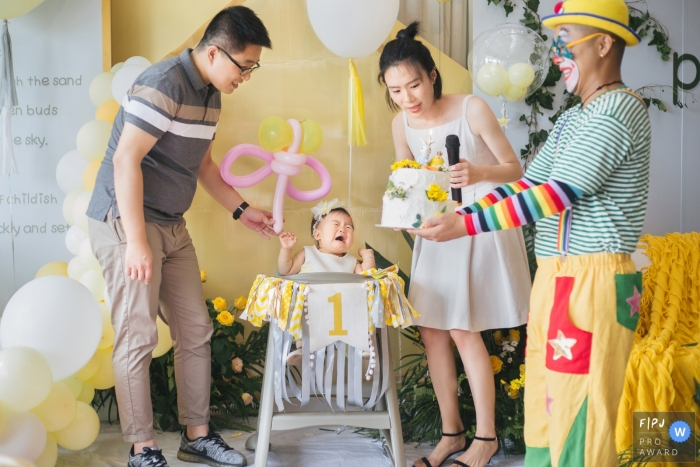 A baby girl cries at her first birthday when she sees a clown carrying the cake in this photo recorded by a Zhejiang, China award-winning, documentary-style family photographer.