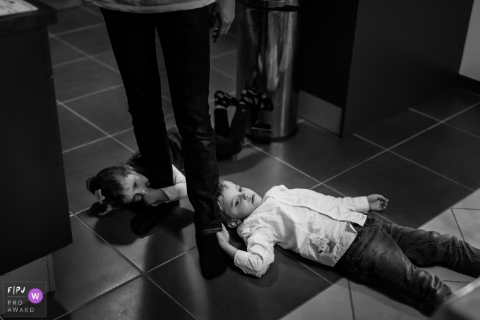 Two children lay on the ground holding onto their parent's legs in this photograph created by a Haute-Garonne family photojournalist.