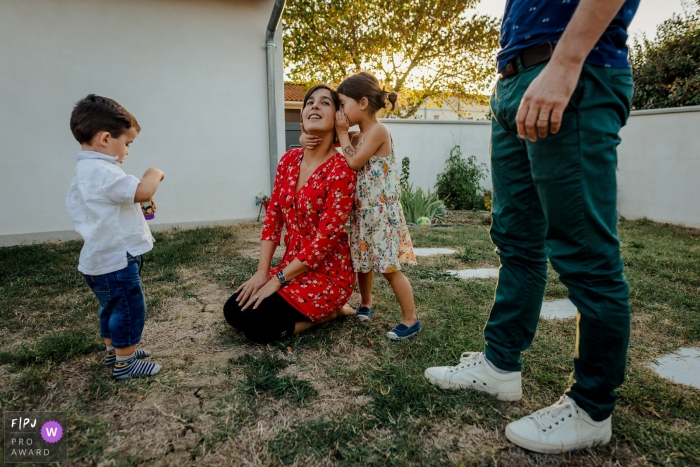 A girl whispers into her mother's ear as the family spends time outside in this Family Photojournalist Association contest awarded photo created by a Haute-Garonne family photographer.
