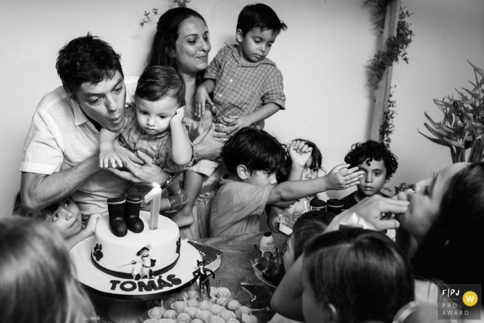 A family celebrates a little boy's first birthday with a cake in this image created by a Rio de Janeiro, Brazil family photographer.