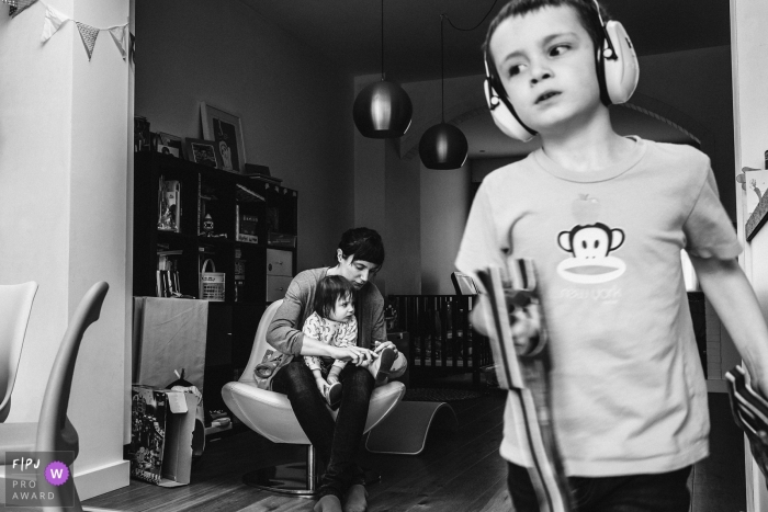 A mother helps her daughter put her shoes on as her son walks in front of them wearing earmuffs in this picture captured by an Antwerpen family photojournalist.