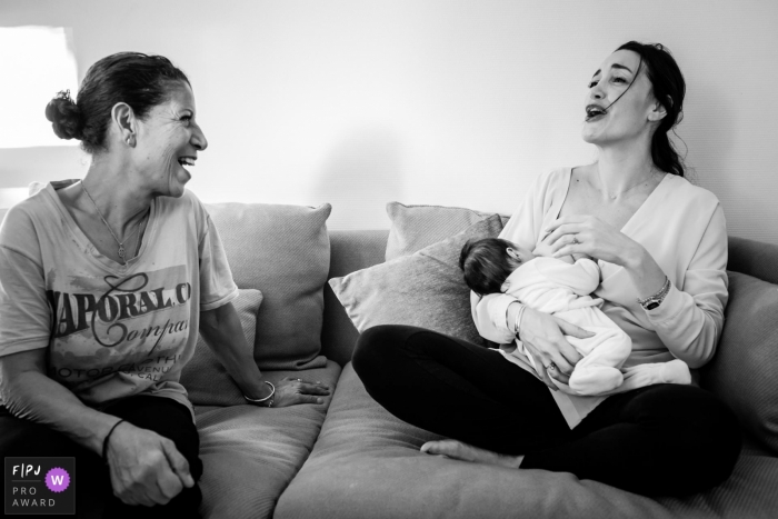 A mother breast feeds her baby as she and another woman have a conversation in this documentary-style family image recorded by a Landes photographer.