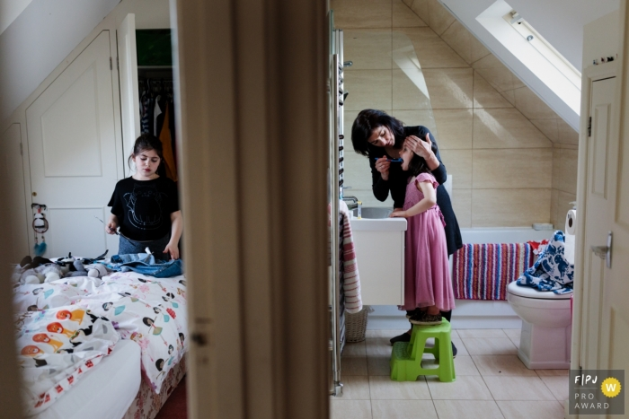 A mother helps her daughter brush her teeth in the bathroom while her other daughter cleans her room in this documentary-style family photo captured by a Kent, England photographer.