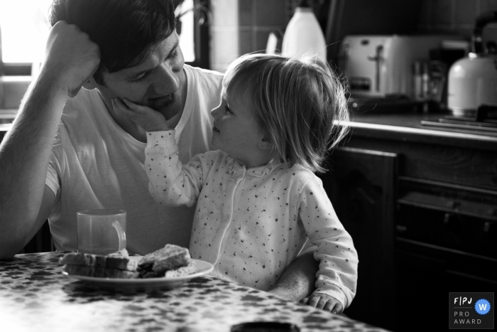 A daughter touches her father's face as they sit together eating breakfast in this Family Photojournalist Association contest awarded photo created by a Scotland family photographer.