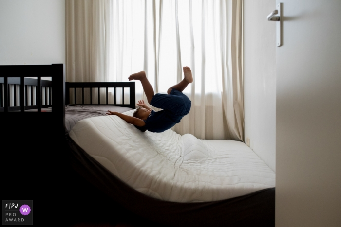A boy jumps onto a mattress on the floor in this FPJA award-winning picture by a Netherlands family photographer.