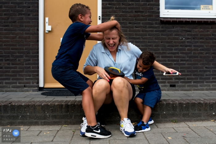 Two little boys tackle their mother as she sits outside in this documentary-style family photo captured by a Netherlands photographer.