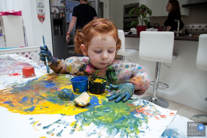 A little girl makes a mess while painting in this photograph by a Scotland documentary family photographer.