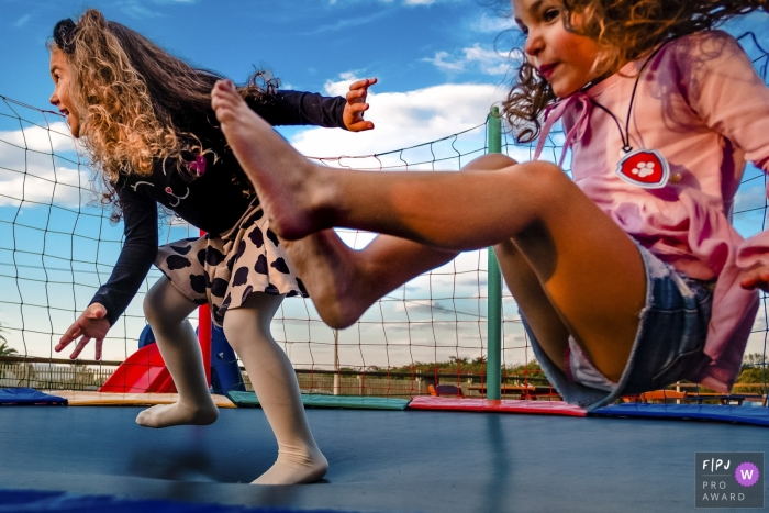 Two girls jump on a trampoline in this award-winning photo by a Rio Grande do Sul, Brazil family photographer.