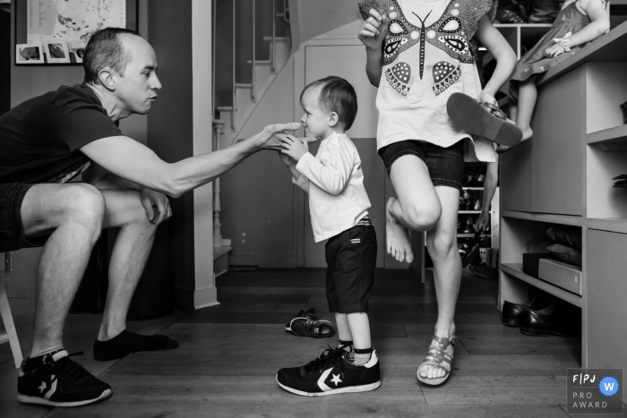 A little boy tries on his father's shoe as the family gets ready to go outside in this picture captured by a Paris, France family photojournalist.