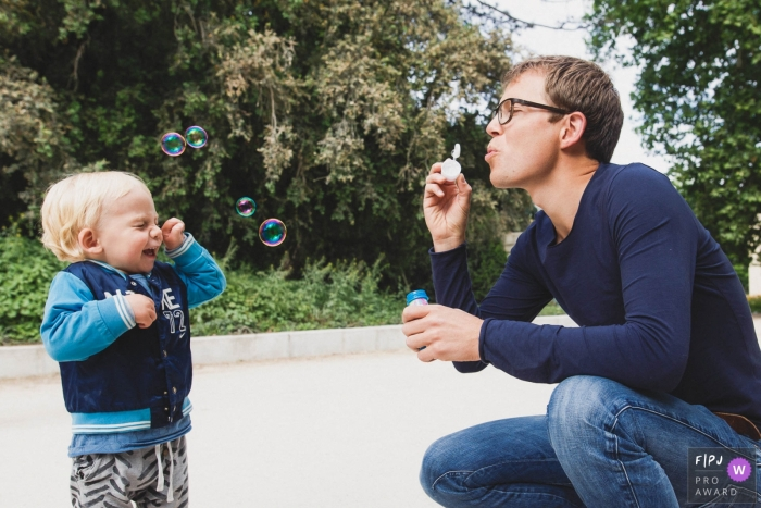 A father blows bubbles for his son in this photo by a Paris, France award-winning family photographer.