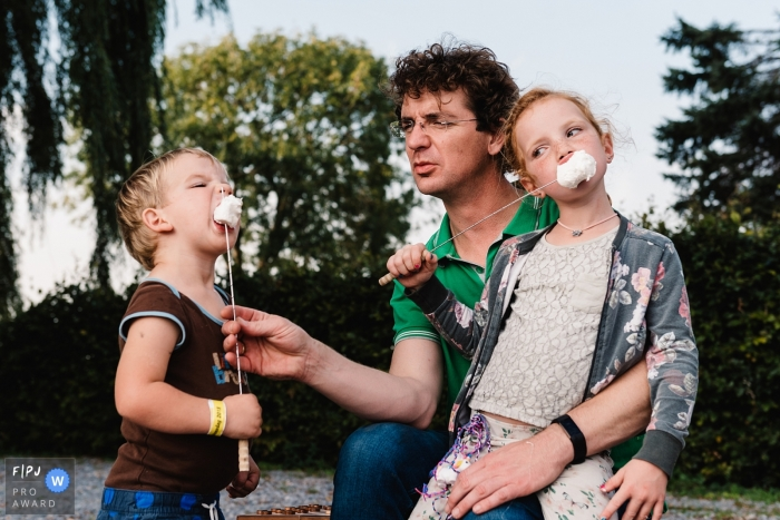 Two children eat toasted marshmallows with their father in this Family Photojournalist Association contest awarded photo created by a Gelderland, Netherlands family photographer.