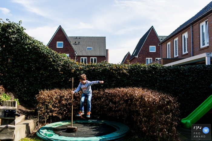 A boy jumps on a trampoline while holding a broom in this award-winning photo by a Modena family photographer.