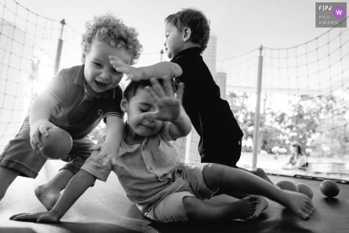 Three little boys play on a trampoline in this award-winning photo by a Florianopolis family photographer.