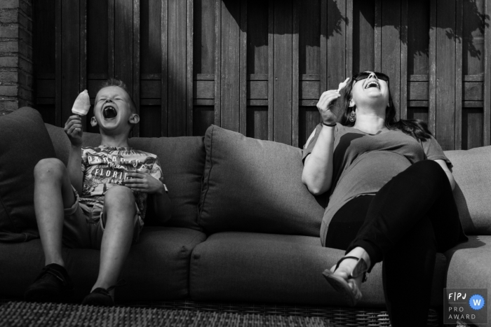 A mother and son laugh as they eat popsicles together in this photograph created by a Netherlands family photojournalist.