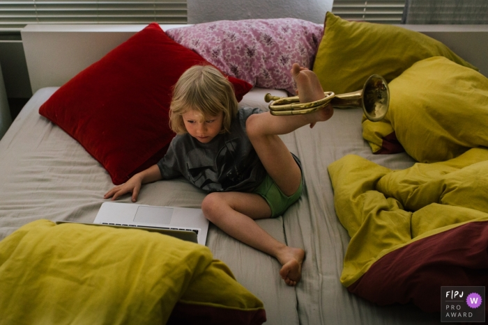 A boy plays with his trumpet on his foot in this Family Photojournalist Association contest awarded photo created by a Netherlands family photographer.