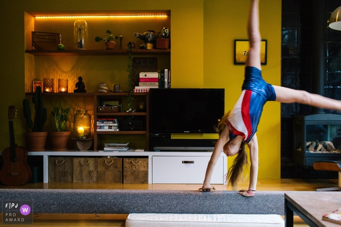 A girl does a cartwheel on a balance beam in this family picture by a Netherlands photographer.