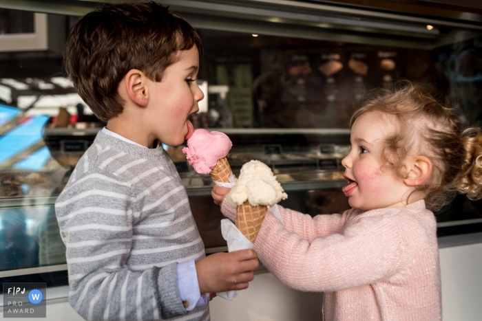 A little girl feeds her bother an ice cream cone in this image created by a Nantes family photographer.