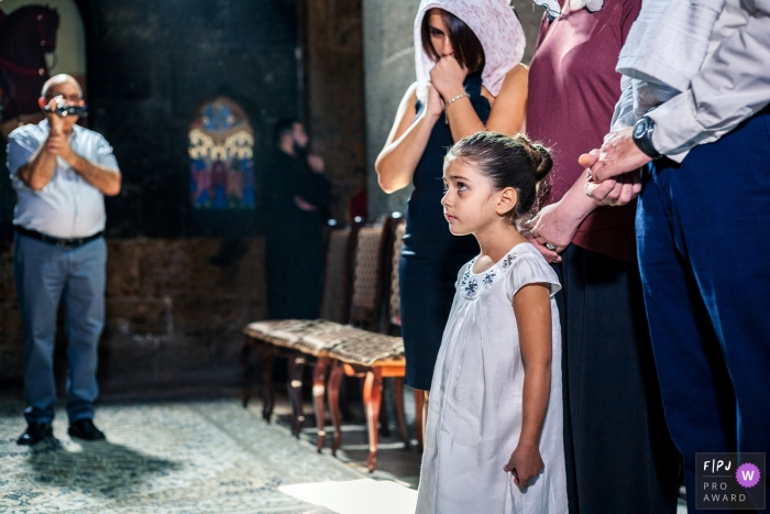 A little girl stands with her family during a ceremony in this documentary-style family image recorded by an Armenia photographer.