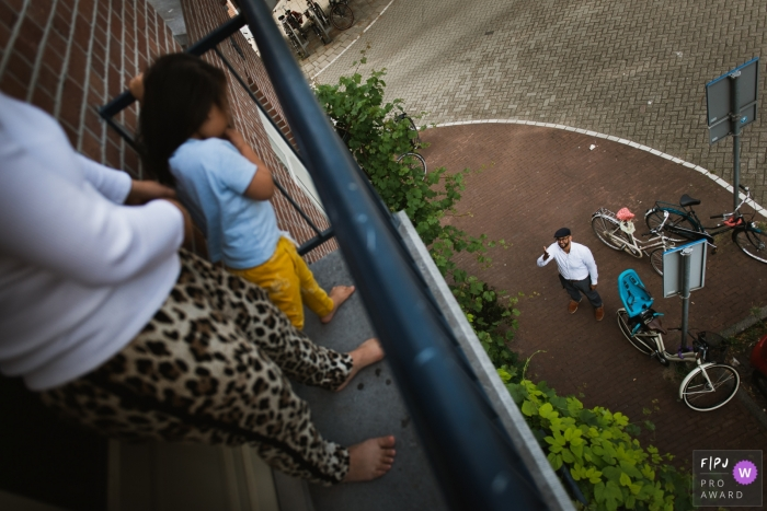 A father waves up to his wife and daughter on a balcony in this award-winning photo by an Amsterdam family photographer.