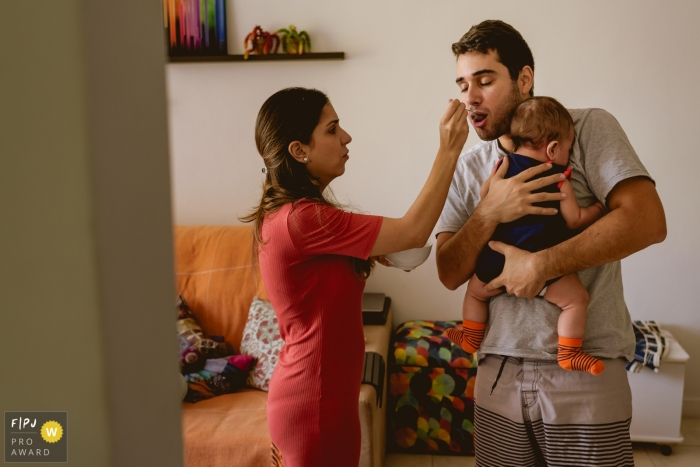 A woman feeds her husband as he uses both arms to hold their baby in this photo recorded by a Rio de Janeiro, Brazil award-winning, documentary-style family photographer.