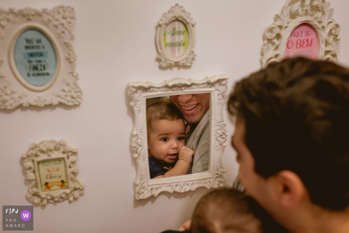 A father and son look in a mirror on the wall in this picture captured by a Rio de Janeiro, Brazil family photojournalist.