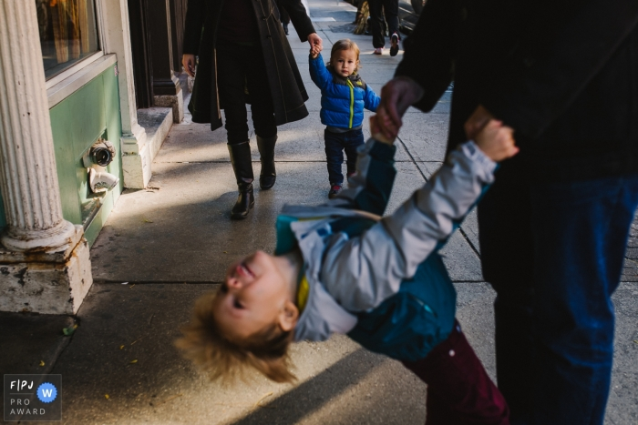 A little boy swings from his father's hands as his mother and little brother walk behind them in this documentary-style family image recorded by a Boston, MA photographer.