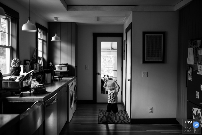 A little boy plays in the kitchen with a plastic container on his head in this Family Photojournalist Association contest awarded photo created by a Boston, MA family photographer.