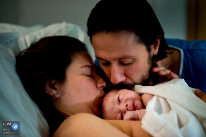 A mother and father kiss their newborn in the hospital in this birth photograph taken by a London, England documentary photographer.
