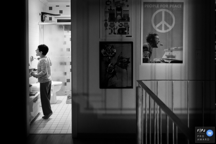 A little boy stands on tiptoe as he brushes his teeth in the bathroom in this award-winning photo by a London, England family photographer.