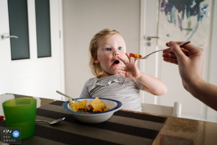 A little girl does not want to eat her lunch and pushes the fork away in this image created by a Netherlands family photographer.