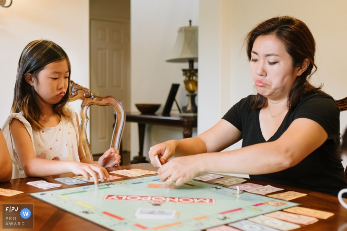 A mother and daughter make the same face as they play Monopoly together in this FPJA award-winning picture by a Los Angeles, CA family photographer.