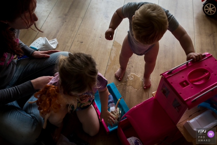 A little boy has an accident on the floor as his mother and sister play with dolls next to him in this FPJA award-winning picture by a Hollands family photographer.