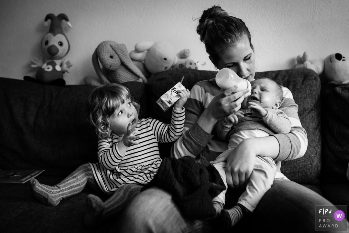 A mother tries to bottle feed her baby as her young daughter holds up her juice box in this documentary-style family photo captured by a Netherlands photographer.