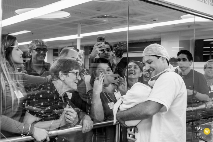 A nurse holds up an infant to the hospital window for its family to see as they gather around and take pictures in this family photo by a Rio de Janeiro, Brazil photographer.
