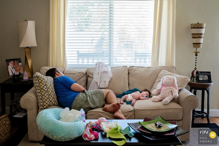 A father sleeps on a couch next to his infant in this photograph by a Key West, FL documentary family photographer.