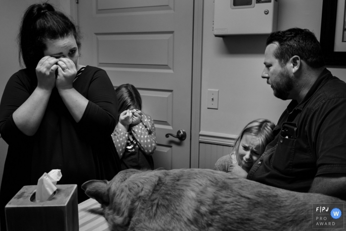 A family cries at the veterinarian's office as they say goodbye to their dog in this FPJA award-winning image captured by a Key West, FL family photographer.