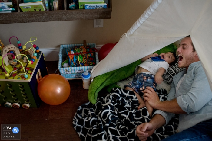 A father plays with his son on his bed as he laughs in this image created by a Key West, FL family photographer.
