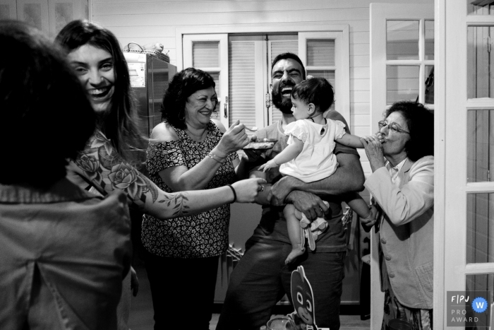 A family gathers around a baby girl as one of them feeds her in this picture captured by a Florianopolis family photojournalist.